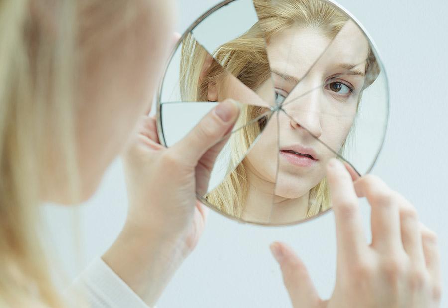 Frau schaut in einen zerbrochenen Spiegel